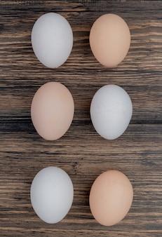 Bovenaanzicht van gezonde kippeneieren gerangschikt in een lijn op een houten achtergrond