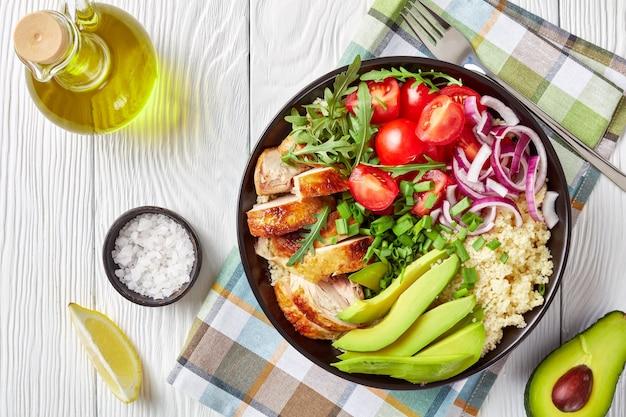 Bovenaanzicht van gezonde kippenkom met gestoomde couscous, verse groenten, avocado, lente-ui en rucola op een witte houten tafel met ingrediënten, horizontale weergave van bovenaf, close-up