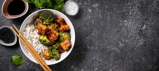 Bovenaanzicht van gezonde kom met gebakken en knapperige tofu, rijst en gestoomde broccoli