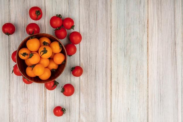 Bovenaanzicht van gezonde oranje tomaten op een houten kom met rode tomaten geïsoleerd op een grijze houten oppervlak met kopie ruimte