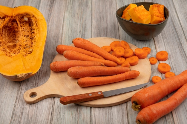 Bovenaanzicht van gezonde plantaardige wortelen op een houten keukenbord met gehakte wortelen met mes met halve pompoen op een grijze houten achtergrond