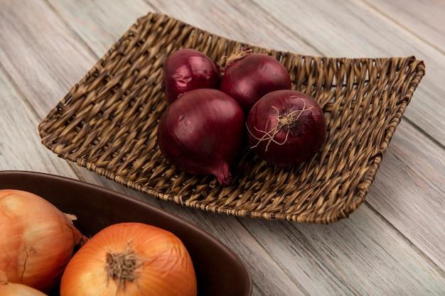 Bovenaanzicht van gezonde rode uien op een rieten dienblad en gele uien op een kom op een grijze houten achtergrond