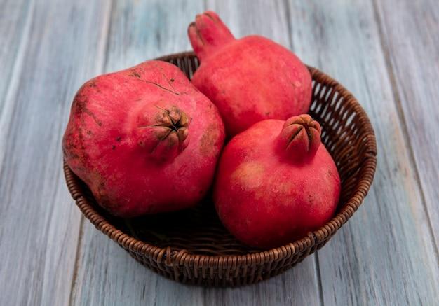 Bovenaanzicht van gezonde rossige granaatappels op een emmer op een grijze achtergrond