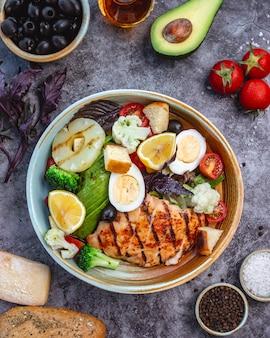 Bovenaanzicht van gezonde voeding salade met gegrilde kip broccoli bloemkool tomaten sla avocado en sla