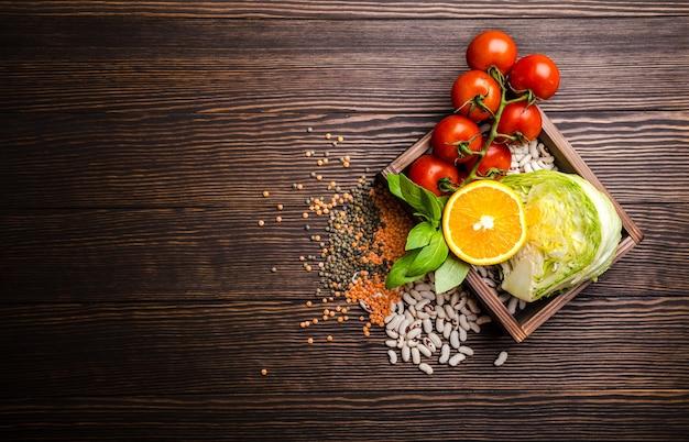 Bovenaanzicht van gezonde voeding voedselingrediënten in houten doos: groenten, bonen, fruit, kruiden met ruimte voor tekst, rustieke houten achtergrond.