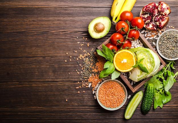 Bovenaanzicht van gezonde voeding voedselingrediënten in houten kist: groenten, bonen, fruit, vis, kruiden met ruimte voor tekst, rustieke houten achtergrond.