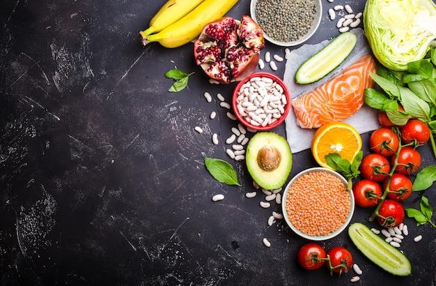 Bovenaanzicht van gezonde voeding voedselingrediënten: vis, zalm, groenten, bonen, fruit, kruiden met ruimte voor tekst, zwarte rustieke stenen achtergrond.