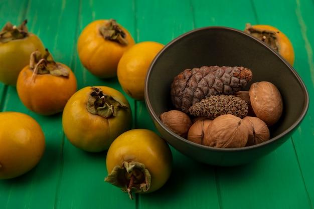 Bovenaanzicht van gezonde walnoten op een kom met kaki fruit geïsoleerd op een groene houten tafel