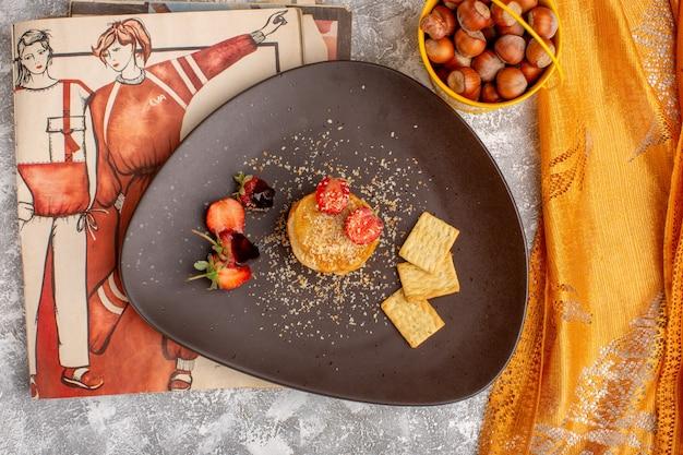 Bovenaanzicht van gezouten chips ontworpen met aardbeien in plaat op de witte tafel, chips snack fruitbes