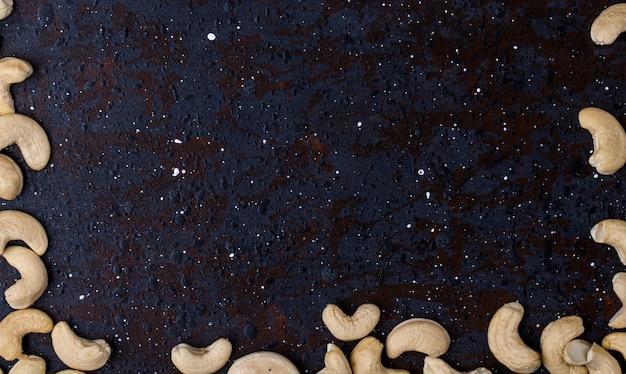 Bovenaanzicht van gezouten geroosterde pistachenoten geïsoleerd op zwarte achtergrond met kopie ruimte