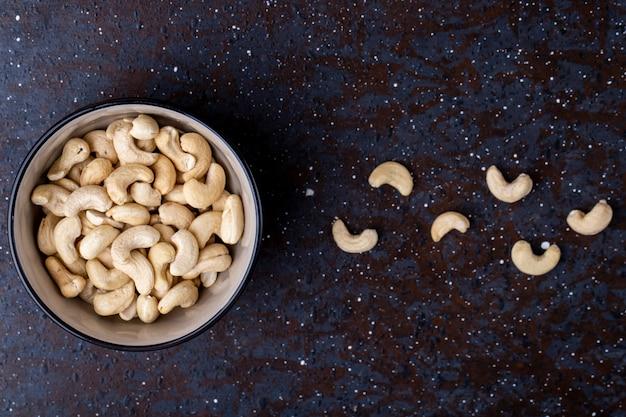 Bovenaanzicht van gezouten geroosterde pistachenoten in een kom op zwarte achtergrond met kopie ruimte