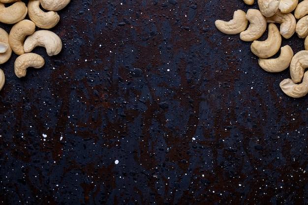 Bovenaanzicht van gezouten geroosterde pistachenoten op zwarte achtergrond met kopie ruimte