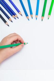 Bovenaanzicht van girl's hand tekenen op wit blanco papier door groen potlood. mock-up. lege ruimte voor tekst.