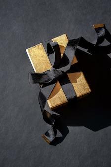 Bovenaanzicht van glanzende gouden kerstcadeau met zwart lint op zwarte achtergrond