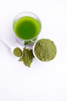 Bovenaanzicht van glas groene groentesap en poeder van groenten op lepel op wit oppervlak