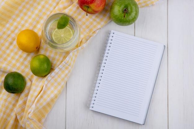 Bovenaanzicht van glas water met limoen en citroen op een gele geruite handdoek met een notitieblok op een wit oppervlak