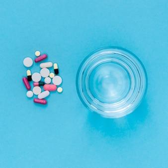 Bovenaanzicht van glas water met pillen