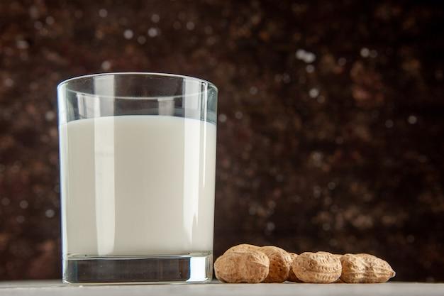 Bovenaanzicht van glazen beker gevuld met melk en droog fruit op donkere achtergrond