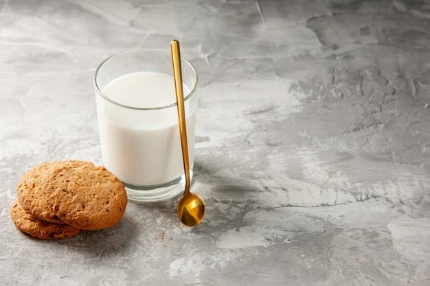 Bovenaanzicht van glazen beker gevuld met melk en gouden lepelkoekjes aan de rechterkant op grijze tafel met vrije ruimte