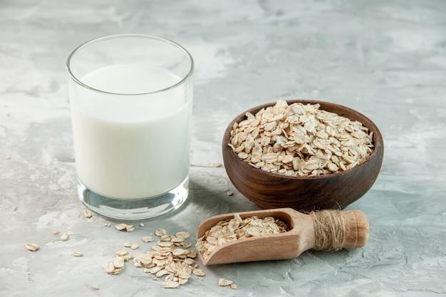 Bovenaanzicht van glazen beker gevuld met melk en haver binnen en buiten de bruine pot op witte achtergrond