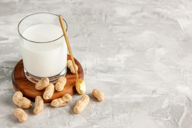 Bovenaanzicht van glazen beker gevuld met melk op houten dienblad en lepel met droog fruit aan de rechterkant op witte achtergrond