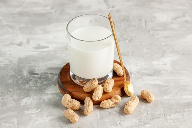 Bovenaanzicht van glazen beker gevuld met melk op houten dienblad en lepel van droog fruit op witte ondergrond