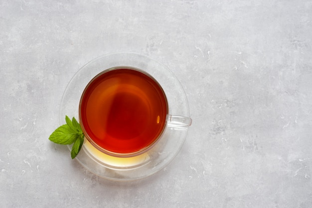 Bovenaanzicht van glazen beker met thee op licht
