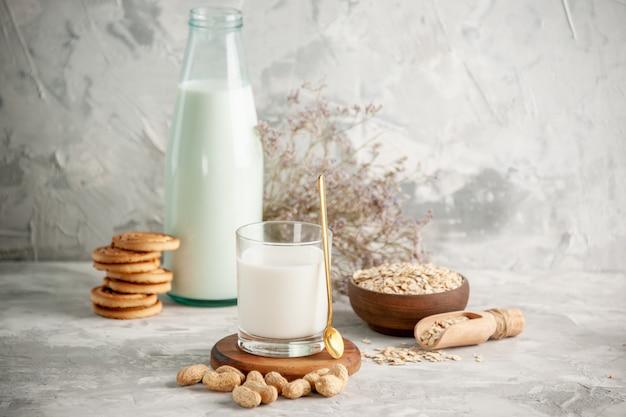 Bovenaanzicht van glazen fles en beker gevuld met melk op houten dienblad en droge vruchten gestapelde koekjes, lepel haver in bruine pot aan de linkerkant op witte tafel op ijsachtergrond