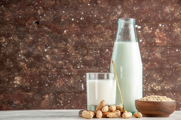 Bovenaanzicht van glazen fles en beker gevuld met melk op houten dienblad en droge vruchten lepel haver in bruine pot aan de linkerkant op witte tafel op bruine achtergrond