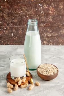 Bovenaanzicht van glazen fles en beker gevuld met melk op houten dienblad en droge vruchten lepel haver in bruine pot op witte tafel op bruine achtergrond