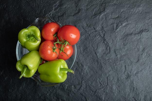 Bovenaanzicht van glazen kom vol met rijpe biologische groenten over zwarte stenen achtergrond