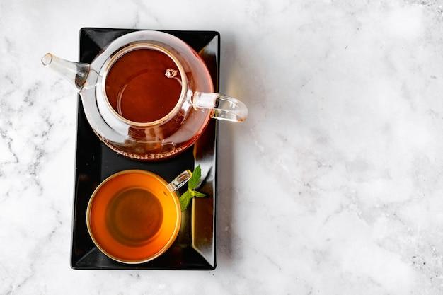 Bovenaanzicht van glazen theekop en glazen waterkoker