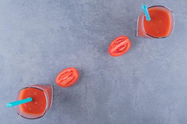 Bovenaanzicht van glazen vers tomatensap en tomaten op een grijze achtergrond.
