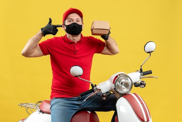 Bovenaanzicht van glimlachende bezorger die rode blouse en muts handschoenen draagt in medische masker zittend op scooter met volgorde