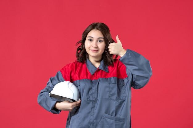 Bovenaanzicht van glimlachende vrouwelijke bouwer in uniform en met harde hoed die een goed gebaar maakt op geïsoleerde rode achtergrond