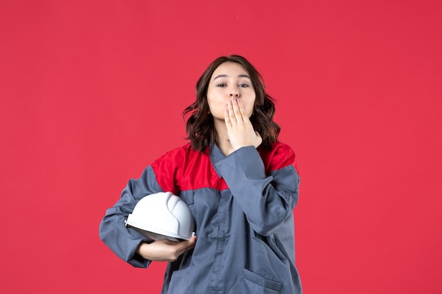 Bovenaanzicht van glimlachende vrouwelijke bouwer in uniform en met harde hoed die kusgebaar maakt op geïsoleerde rode achtergrond