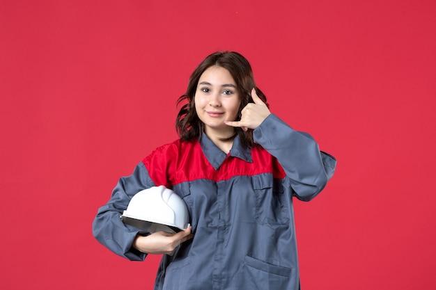 Bovenaanzicht van glimlachende vrouwelijke bouwer in uniform en met harde hoed die me een gebaar maakt op geïsoleerde rode achtergrond