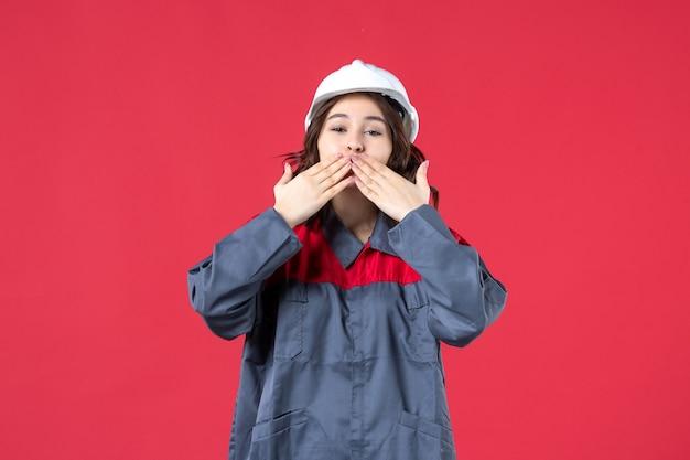 Bovenaanzicht van glimlachende vrouwelijke bouwer in uniform met harde hoed en kusgebaar maken op geïsoleerde rode achtergrond