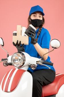 Bovenaanzicht van glimlachende vrouwelijke koerier met een zwart medisch masker en handschoenen die bestellingen op perzik afleveren