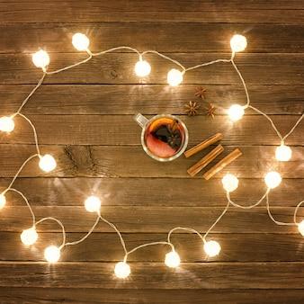 Bovenaanzicht van glühwein met kruiden, kaneelstokjes, steranijs. houten tafel. lantaarns.