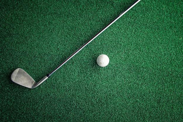 Bovenaanzicht van golfclub en bal op golfbaan.