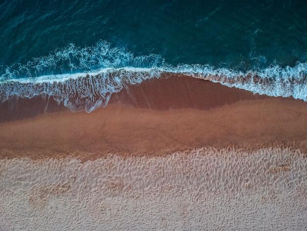 Bovenaanzicht van golven op het zandstrand op het eiland kreta