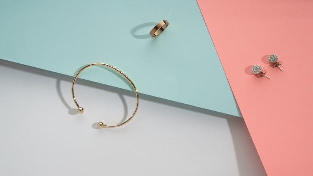 Bovenaanzicht van gouden accessoires op geometrische pastelkleuren achtergrond