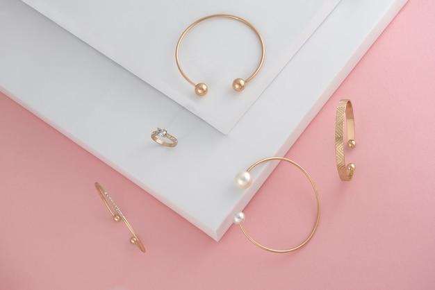 Bovenaanzicht van gouden accessoires op roze en witte achtergrond met kopieerpasta