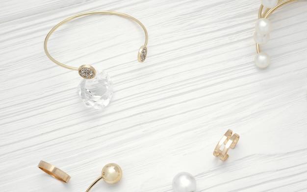 Bovenaanzicht van gouden armband op diamant en gouden sieraden op houten tafel