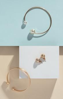 Bovenaanzicht van gouden armbanden en paar oorbellen op pastelkleurenpapier