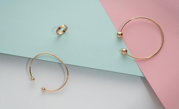 Bovenaanzicht van gouden armbanden en ring op geometrische pastel kleur achtergrond