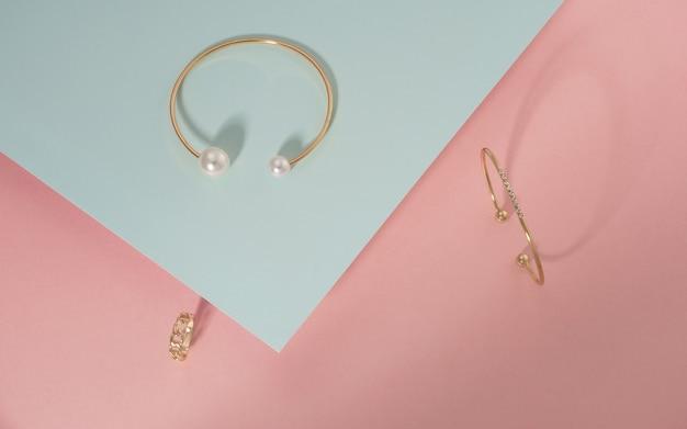 Bovenaanzicht van gouden armbanden en ring op roze en blauwe achtergrond met kopie ruimte