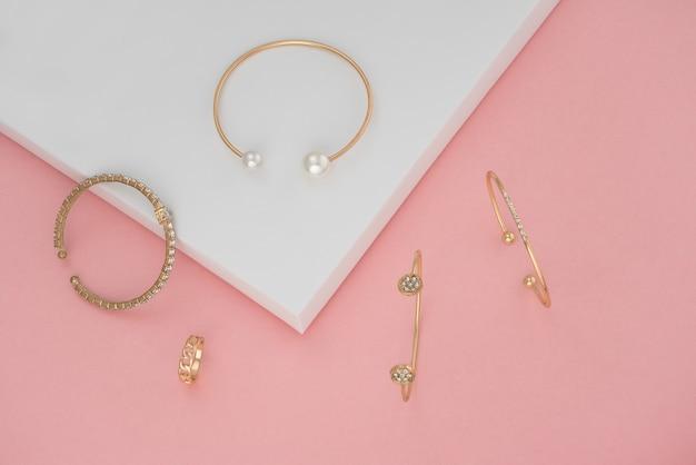 Bovenaanzicht van gouden armbanden en ring op roze en wit papier achtergrond