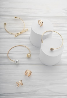 Bovenaanzicht van gouden armbanden en ringen op witte houten oppervlak met kopie ruimte